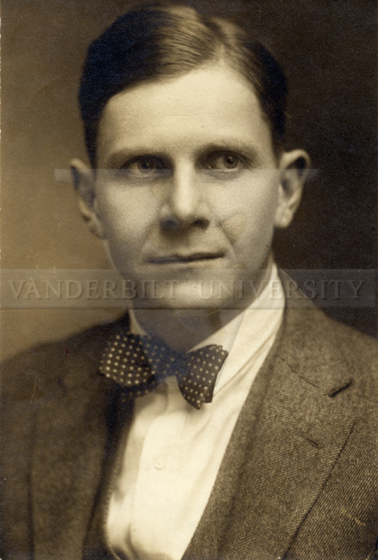 Sepia-colored photo of John Crowe Ransom weading a bow-tie with slicked-down hair.