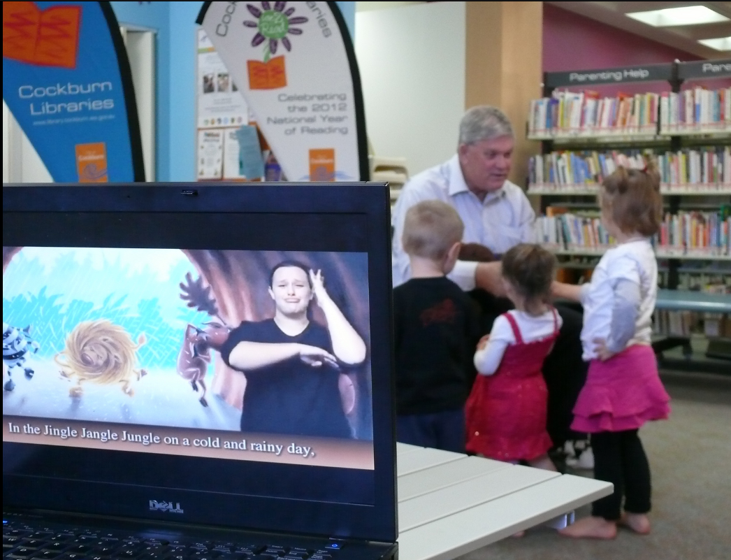 Computer screen with woman signing along to storybook, small children in background
