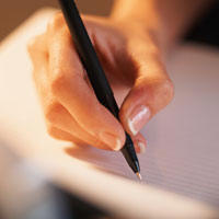 Image of a hand writing with a pen on paper