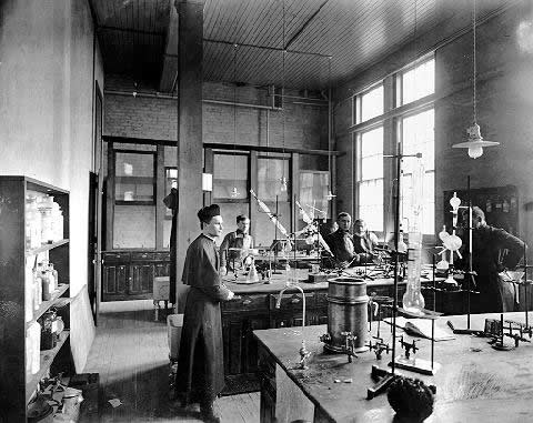 Father Julius Nieuwland, dressed in priest's robes, and several assistants work in a chemistry laboratory