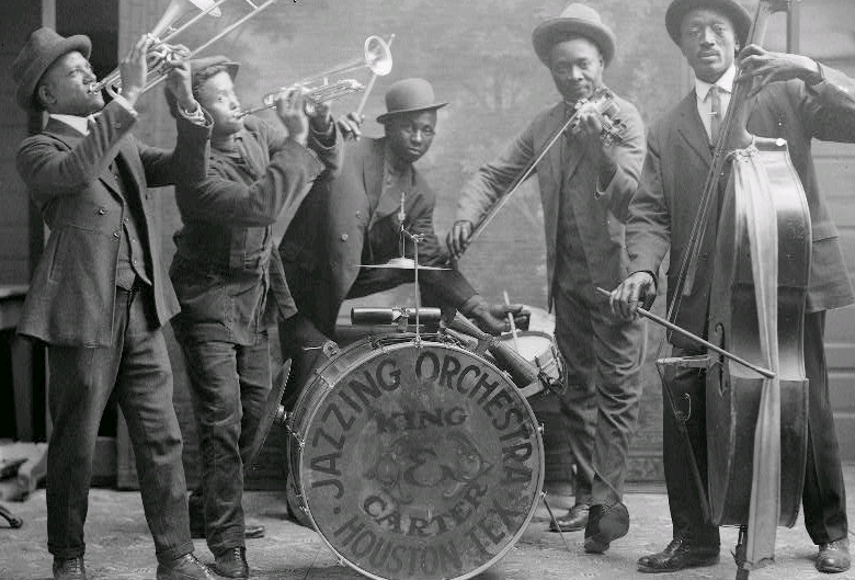 Five black men in suits and hats play a trombone, trumpet, drum set, violin, and bass viol in a band. King Carter Jazzing Orchestra, Houston, TX is written on the bass drum.