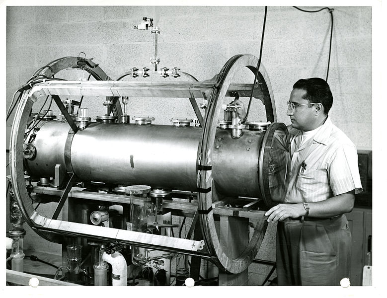 A man stands next to a complicated machine, the atomic clock