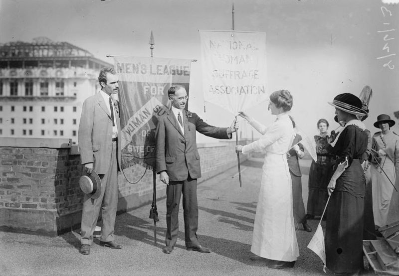 "A group of women carry pennants, and two men stand next to a banner saying ""Men's League for Woman Su."" One man and one woman together hold a banner that says ""Woman Suffrage Association."""