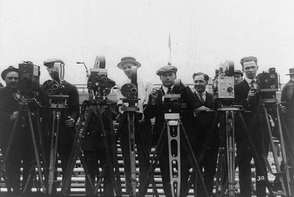 Several photographers in suits and hats with old-fashioned video cameras face the viewer