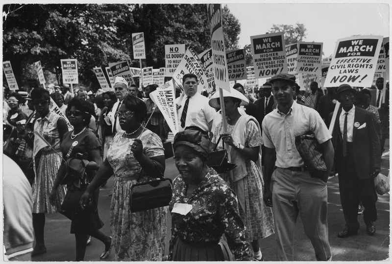 A crowd of black Americans and a few white men march down a street carrying signs stating that they are marching for civil rights.