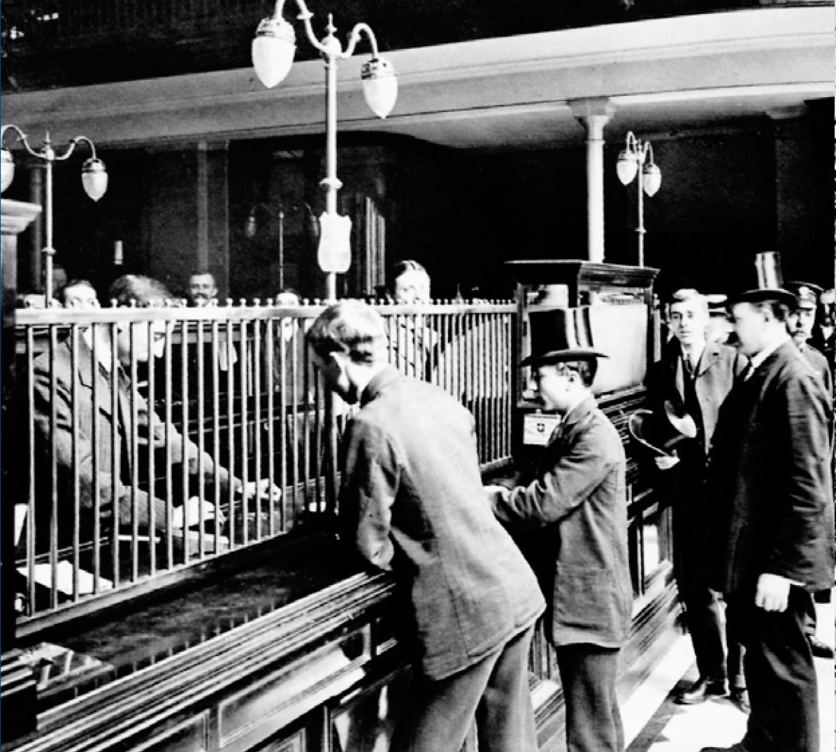 At a bank counter, customers dressed in suits do business. Iron bars separate the customers from the bank tellers.