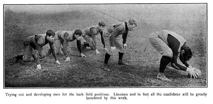 Five men are in a football formation wearing old-fashioned uniforms. One man prepares to hike the ball.