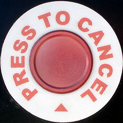 """Picture of a round red button, with red """"Press to Cancel"""" texts wrapping around."""