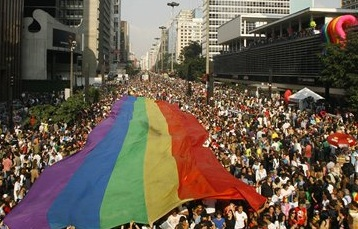Parade scene with rainbow banner unfurled over a large crowd of people