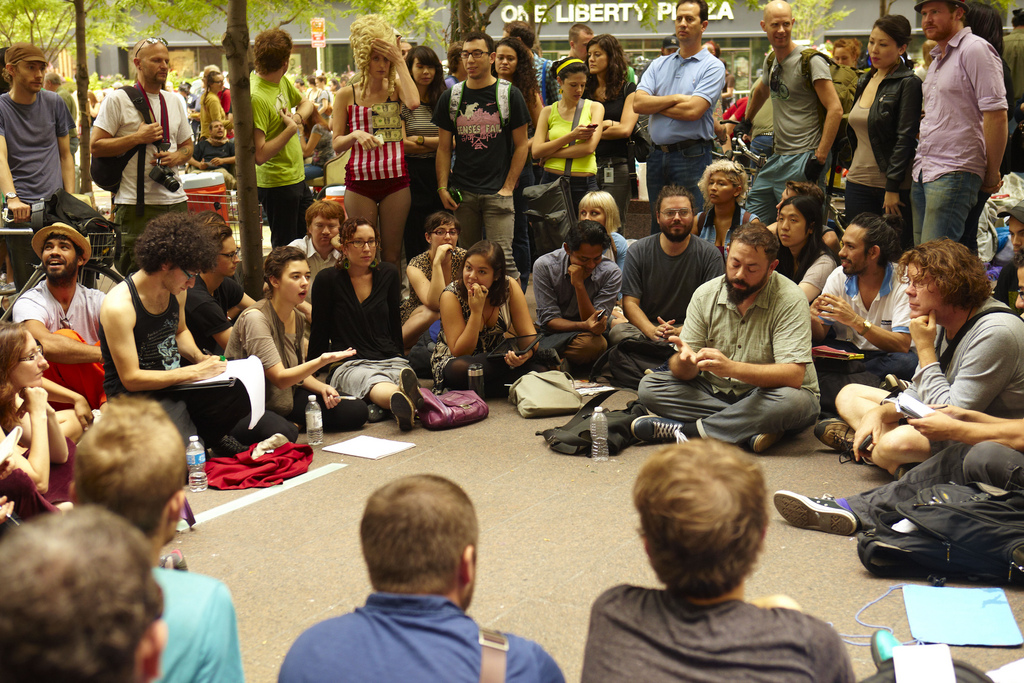 photograph of a dicussion taking place between people sitting in a circle during the Occupy Wallstreet movement