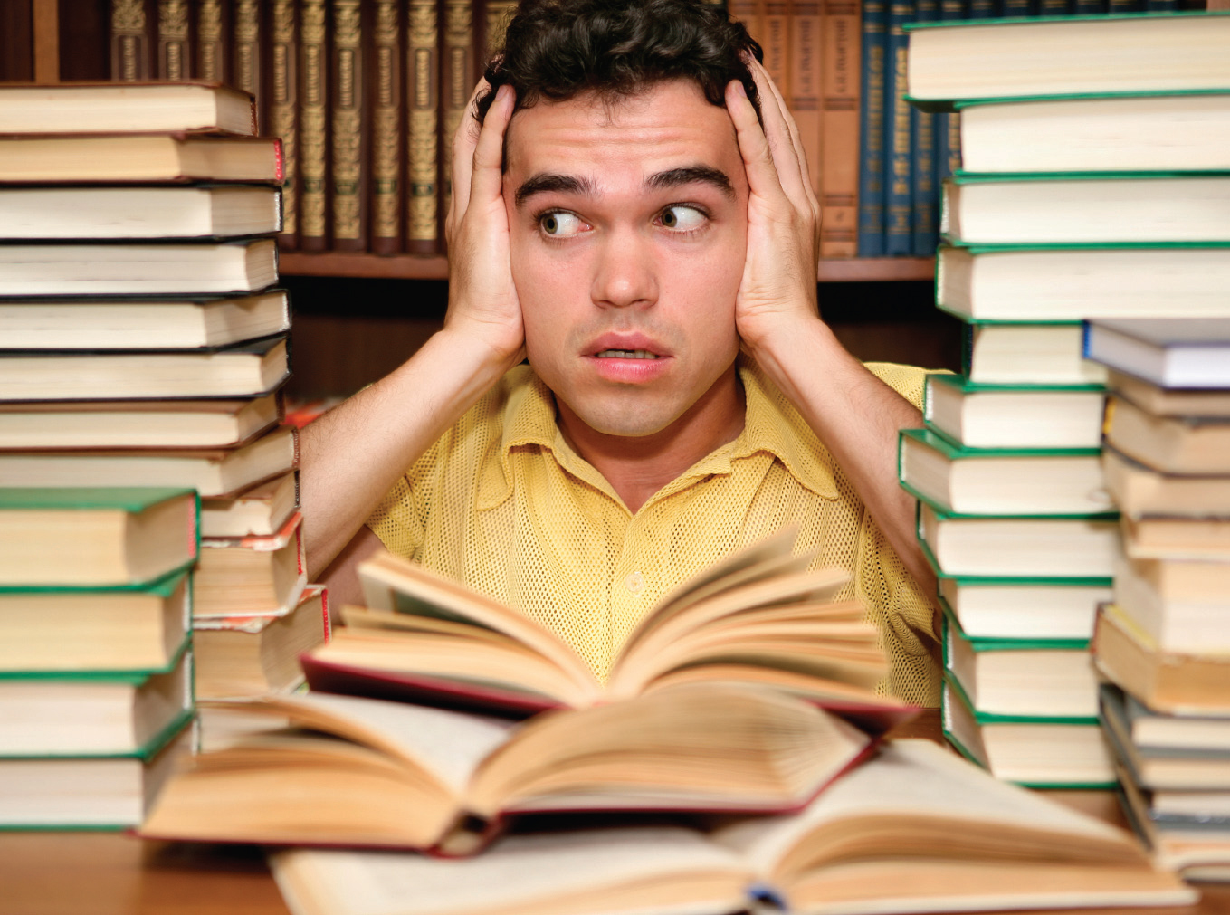 Man surrounded by stacks of books looking anxious