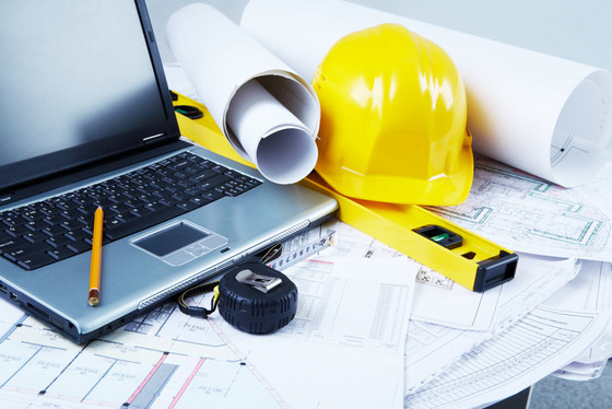 Laptop computer with hard hat, blueprints and construction management equipment