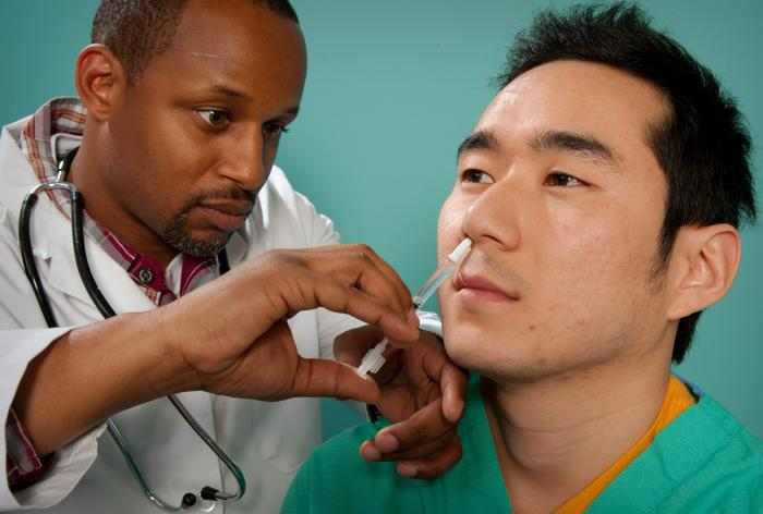 This 2009 image depicts a healthcare practitioner as he was administering the H1N1 live attenuated intranasal vaccine (LAIV) to an Asian man. Using a small syringe, he was delivering the vaccine mist into the man's right nostril.