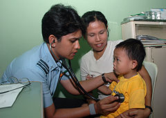 Indian Air Force physician Bharathi Mahapatra examines a young boy's heart rate at the Gunungsitoli General Hospital.