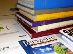 Books and journals in neat piles to show sources of literature