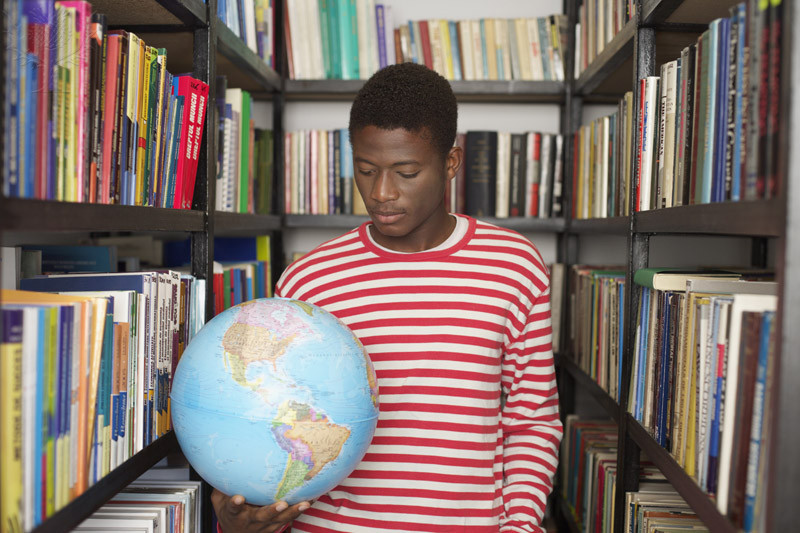 young man in library with globe