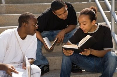 three African American males reading books together