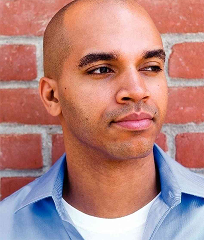 Photograph of Kadir Nelson with brick wall in background.