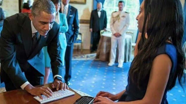 President Barack Obama, a black man with black and grey hair in a blue suit, typing to Haben Girma, a black woman with long dark hair in a blue dress.