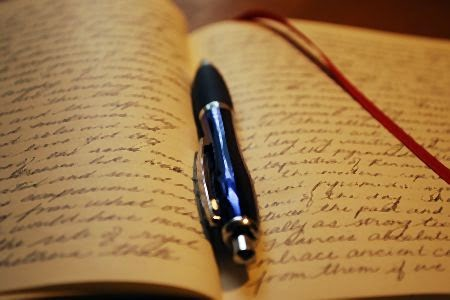 pen in a journal with script writing