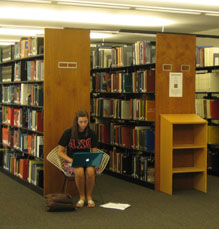 student with laptop studying in front of reference stacks