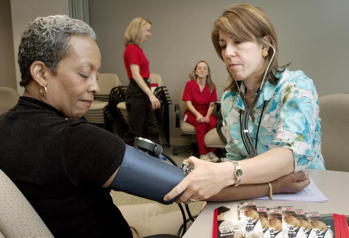 health professional taking patient's blood pressure