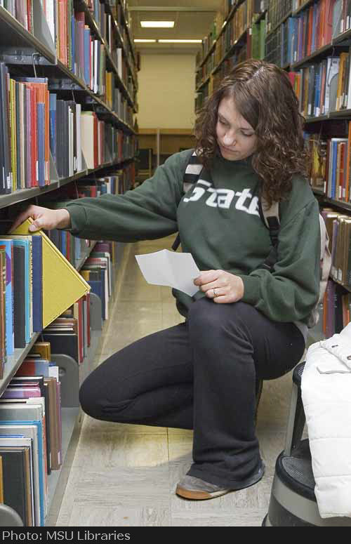 Student retrieving book from library stacks