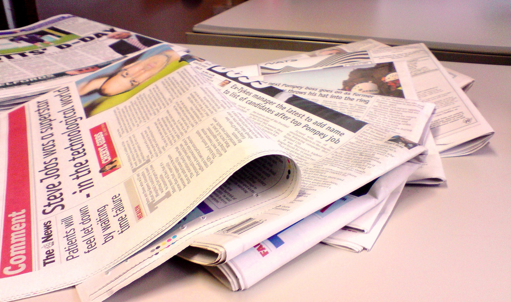 Newspaper sections spread out on a table, Image from flickr, user NS Newsflash