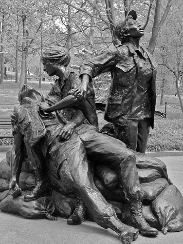 Photo of Vietnam Women's Memorial sculpture of one nurse holding a hurt soldier with a woman standing with them.