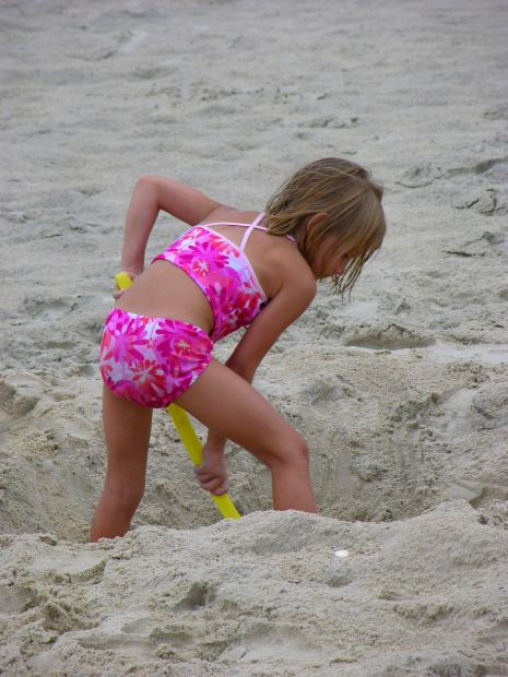 Photo of girl digging on beach
