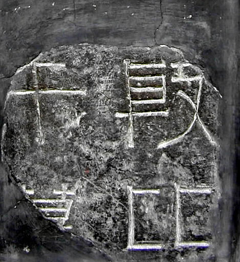 Four Chinese characters engraved on a tombstone