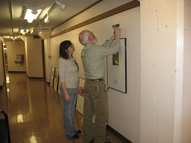 Paul Brower or the Western Gallery demonstrates how to hang the artwork