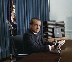 President Nixon holding a sheaf of papers as he sits behind a desk with two microphones on it.
