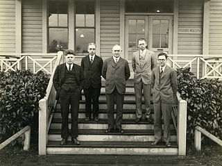 a black and white photo of five suited men standing on a short set of stairs.