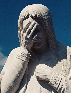 Statue of Jesus with hand on face.