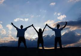 three people holding hands up in to the sky in triumph