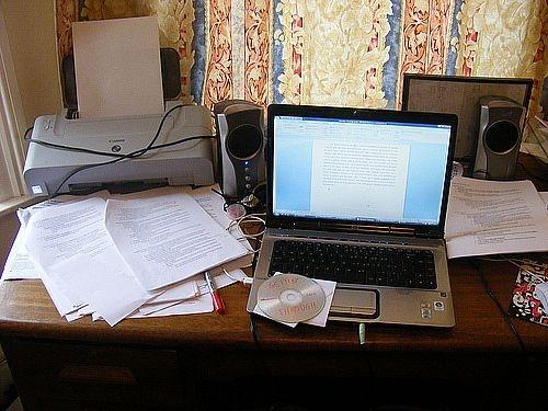 Laptop next to printer on desk