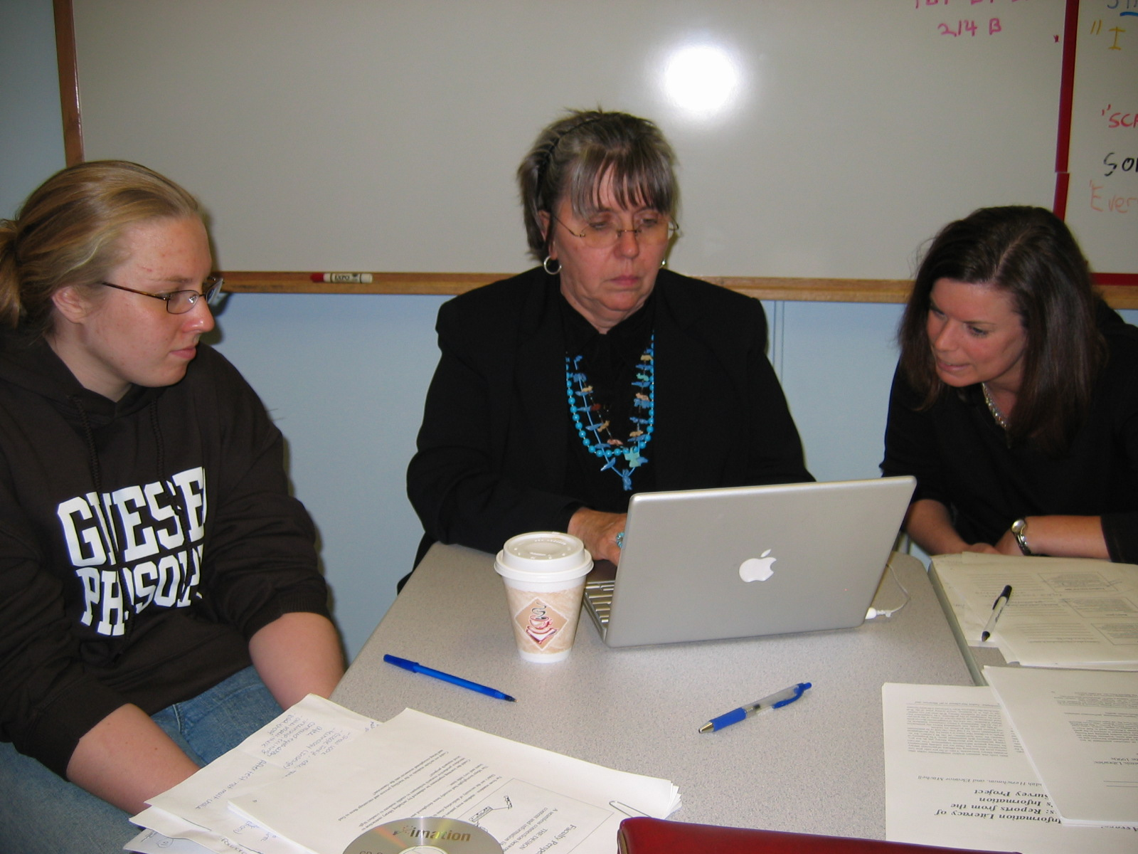 Image of librarian, professor and student working together