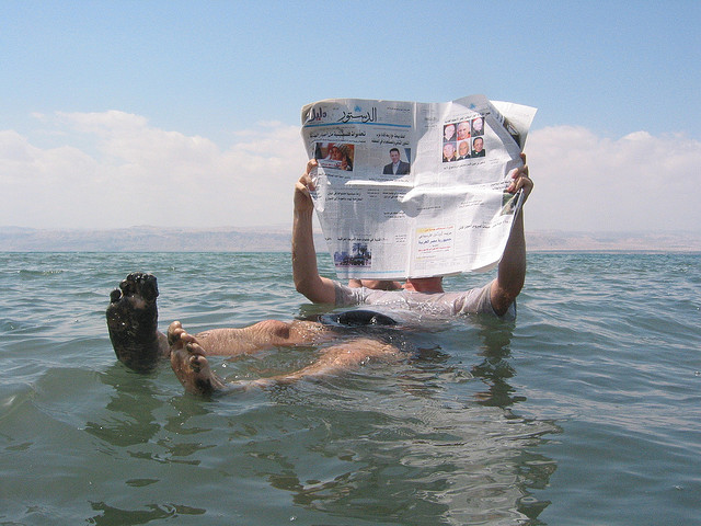 man reading a newspaper while floating in the dead sea