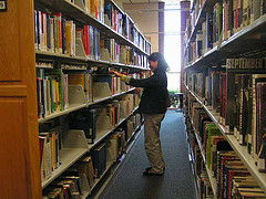 person looking at books, photo by NJLA: New Jersey Library Association,  https://www.flickr.com/photos/njla/4009541750/
