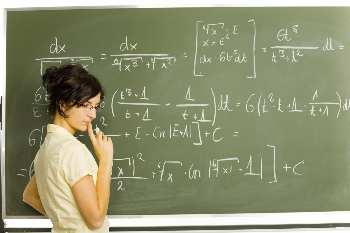 Picture of woman thinking in front of a chalk board