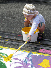 Toddler with paint bucket paints on the ground