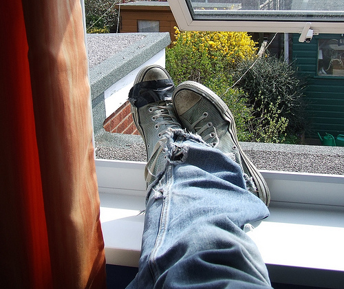 Sneakered feet lounging on window sill