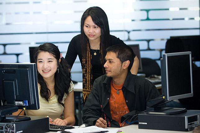 Students conferring at a computer screen