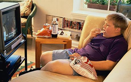 obese child eats junk food in front of television