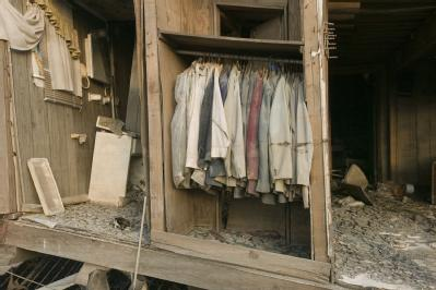 A closet with suits hanging exposed to the outside elements at a home that was destroyed in the Lower 9th Ward due to Hurricane Katrina