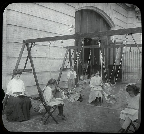 Women and girls reading near swingset where younger children are suspended in hammock like swings, July 1910.. Hine, Lewis Wickes -- Photographer. 1910