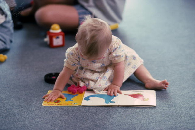 Blonde toddler sitting on floor leaning over picture book