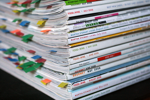 a stack of periodicals viewed from the top corner with many little coloured tabs sticking out of the top