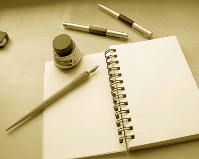 image of ink, pen, and open notebook